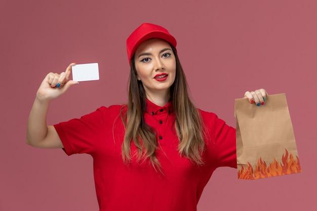 Weiblicher kurier der vorderansicht in der roten uniform, die weiße karte und lebensmittelpaket auf der rosa hintergrunddienstauftragslieferuniformfirma hält