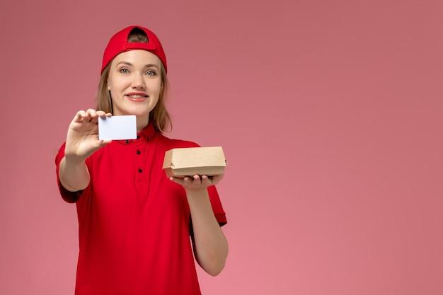 Weiblicher kurier der vorderansicht in der roten uniform und im umhang, der kleines liefernahrungsmittelpaket mit weißer plastikkarte hält, die auf rosa wand lächelt, servicejobuniformlieferung