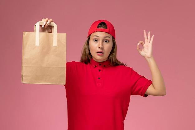 Weiblicher kurier der vorderansicht in der roten uniform und im umhang, der lieferpapierpaket an der rosa wand hält, einheitlicher lieferservice