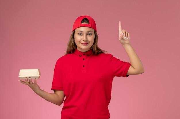 Weiblicher kurier der vorderansicht in der roten uniform und im umhang, der lieferung-nahrungsmittelpaket auf hellrosa hintergrundarbeiteruniform-lieferservice-firmenjob hält