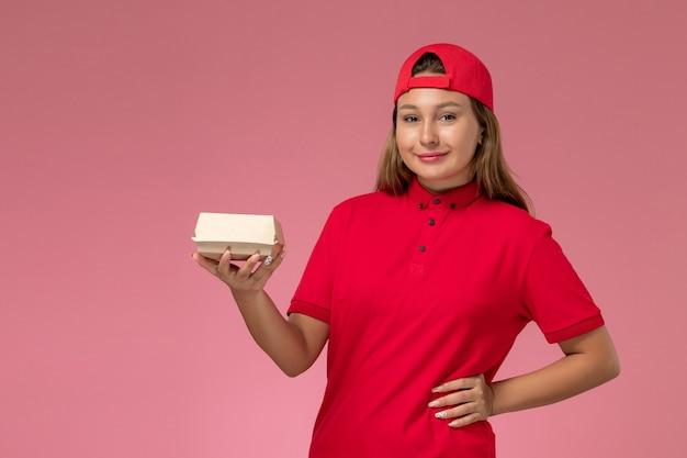 Weiblicher kurier der vorderansicht in der roten uniform und im umhang, der lieferung-nahrungsmittelpaket auf hellrosa hintergrunduniform-lieferservice-firmenjobarbeiter hält