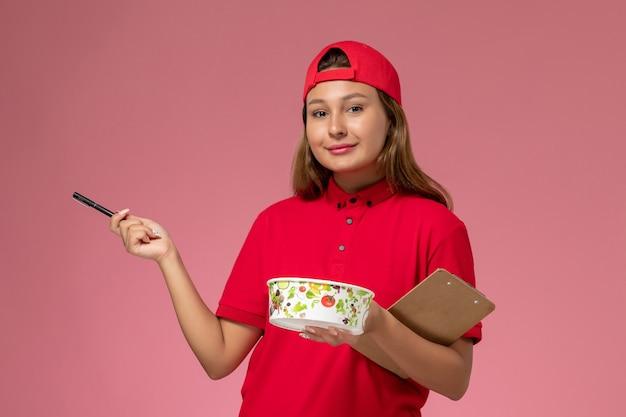 Weiblicher kurier der vorderansicht in der roten uniform und im umhang, der notizblock und lieferschüssel auf rosa hintergrundjobarbeitsuniform-lieferservice hält