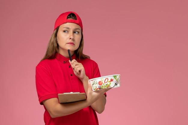 Weiblicher kurier der vorderansicht in der roten uniform und im umhang, der notizblock und lieferschüssel hält, die auf dem rosa hintergrunduniformlieferdienstjobarbeiter denken