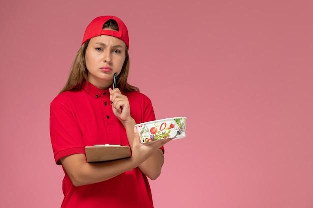 Weiblicher kurier der vorderansicht in der roten uniform und im umhang, der notizblock und lieferschüssel hält, die auf rosa hintergrunduniform-lieferservicejob denken