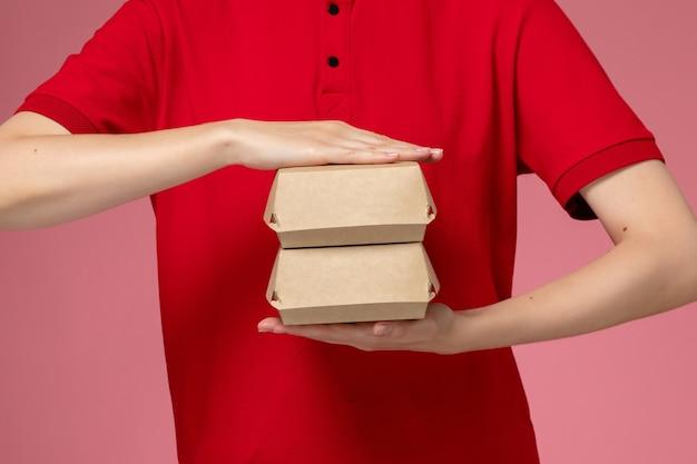 Weiblicher kurier der vorderansicht in der roten uniform und im umhang, die kleine liefernahrungsmittelpakete auf hellrosa wand halten, lieferserviceunternehmensuniformjobarbeiter