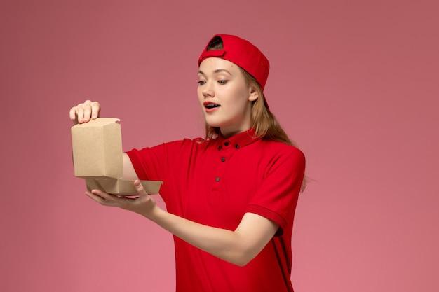 Weiblicher kurier der vorderansicht in der roten uniform und im umhang, die kleines liefernahrungsmittelpaket auf der uniformarbeit des rosa schreibtischlieferdienstes halten