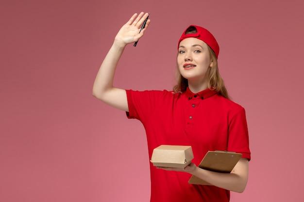 Weiblicher kurier der vorderansicht in der roten uniform und im umhang, die kleines liefernahrungsmittelpaket mit notizblock und stift auf rosa wand halten, dienstuniform-lieferarbeiterjobarbeit