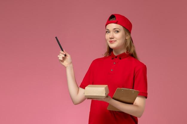 Weiblicher kurier der vorderansicht in der roten uniform und im umhang, die kleines liefernahrungsmittelpaket mit notizblock und stift auf rosa wand halten, dienstuniform-lieferarbeiterjobarbeitsmädchen