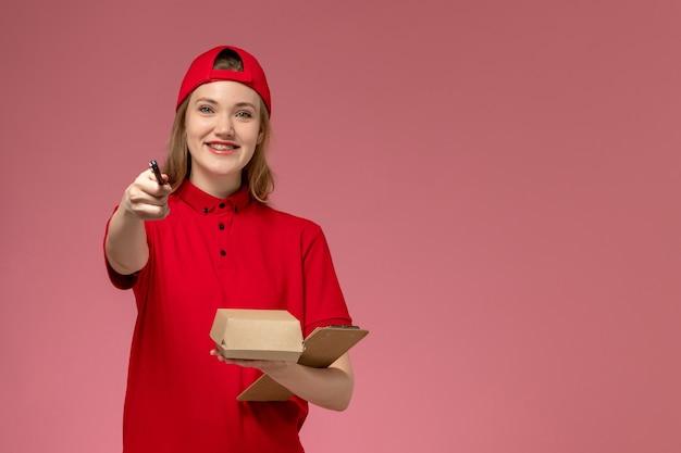 Weiblicher kurier der vorderansicht in der roten uniform und im umhang, die kleines liefernahrungsmittelpaket mit notizblock und stift auf rosa wand halten, serviceuniform-lieferjobarbeiter