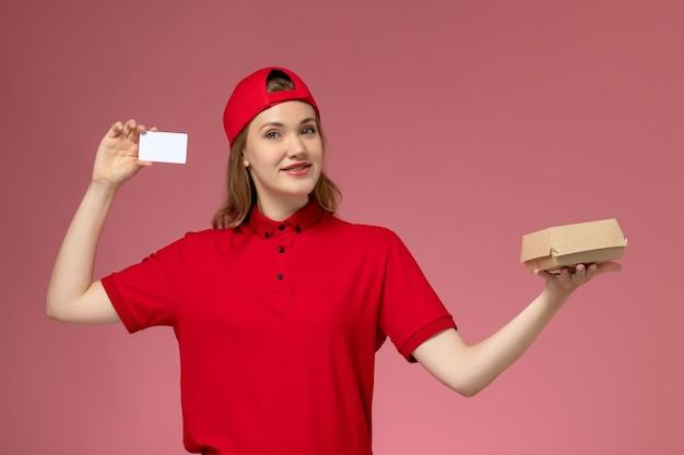 Weiblicher kurier der vorderansicht in der roten uniform und im umhang, die kleines liefernahrungsmittelpaket mit weißer plastikkarte auf der rosa wand halten, servicejobuniformlieferung