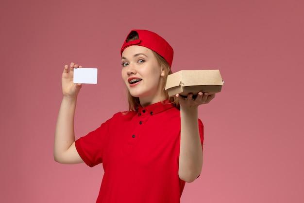 Weiblicher kurier der vorderansicht in der roten uniform und im umhang, die kleines liefernahrungsmittelpaket mit weißer plastikkarte auf hellrosa wand halten, servicejobuniformlieferung