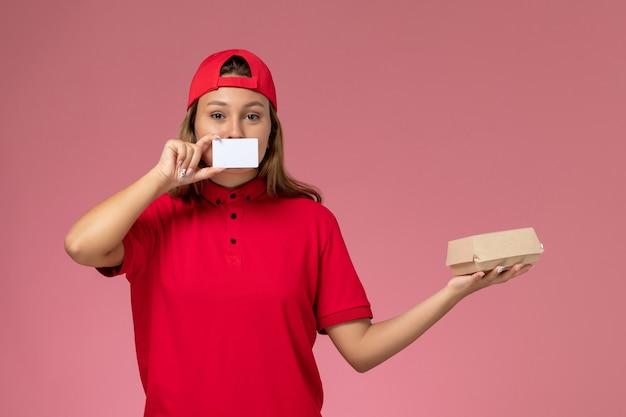 Weiblicher kurier der vorderansicht in der roten uniform und im umhang, die kleines liefernahrungsmittelpaket und -karte auf hellrosa wand halten, einheitlicher jobarbeiter-lieferservice