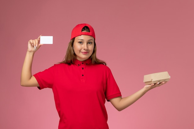 Weiblicher kurier der vorderansicht in der roten uniform und im umhang, die kleines liefernahrungsmittelpaket und -karte auf hellrosa wand halten, einheitlicher lieferservicejob