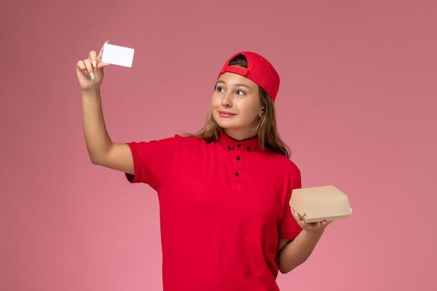 Weiblicher kurier der vorderansicht in der roten uniform und im umhang, die kleines liefernahrungsmittelpaket und karte auf rosa wand halten, einheitliche lieferservicejobarbeit