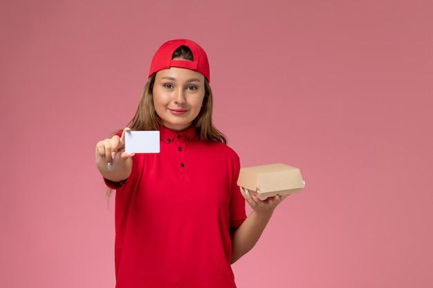 Weiblicher kurier der vorderansicht in der roten uniform und im umhang, die kleines liefernahrungsmittelpaket und karte auf rosa wand halten, einheitlicher lieferarbeiter-servicejob