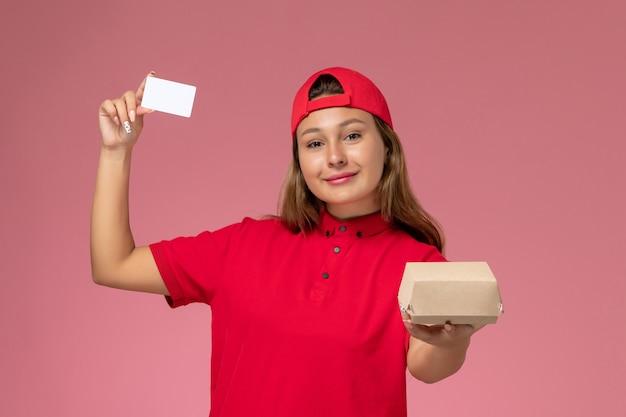 Weiblicher kurier der vorderansicht in der roten uniform und im umhang, die kleines liefernahrungsmittelpaket und karte auf rosa wand halten, einheitlicher lieferservicearbeiter