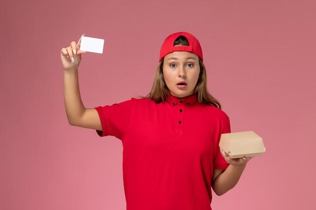 Weiblicher kurier der vorderansicht in der roten uniform und im umhang, die kleines liefernahrungsmittelpaket und karte auf rosa wand halten, einheitlicher lieferservicejobarbeiter