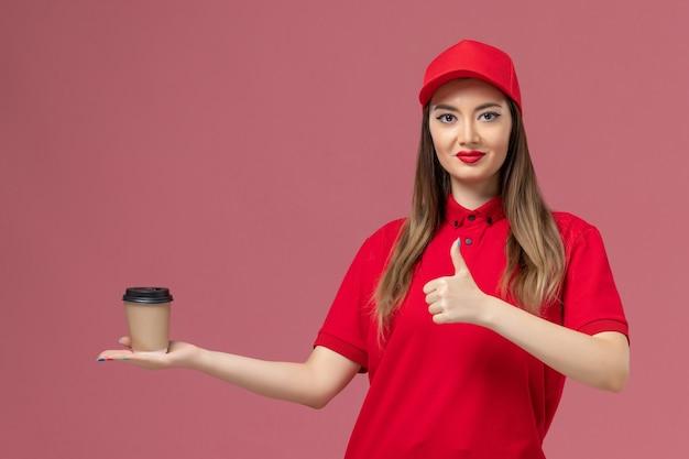 Weiblicher kurier der vorderansicht in der roten uniform und im umhang, die lieferung kaffeetasse lächelnd auf dem rosa hintergrund service delivery uniform jobarbeiter lächeln