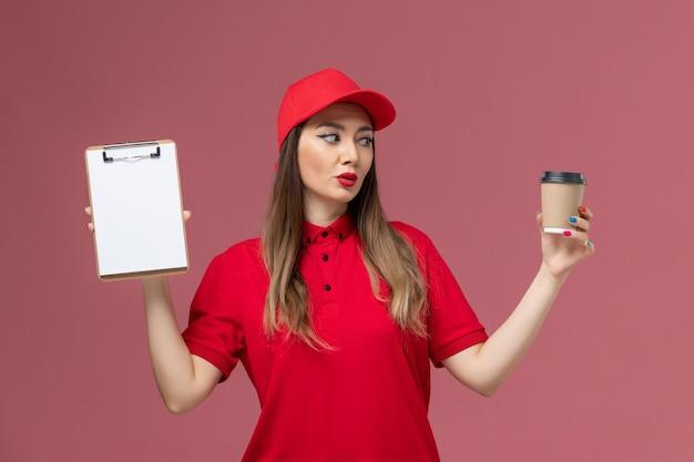 Weiblicher kurier der vorderansicht in der roten uniform und im umhang, die lieferung kaffeetasse mit notizblock auf der rosa hintergrunddienstauftragslieferuniform halten