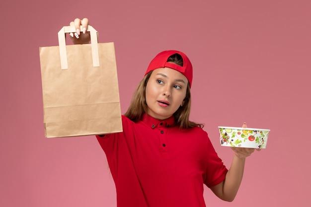 Weiblicher kurier der vorderansicht in der roten uniform und im umhang, die lieferung lebensmittelpaket und schüssel auf der rosa wand halten, einheitlicher zustellungsjobdienst