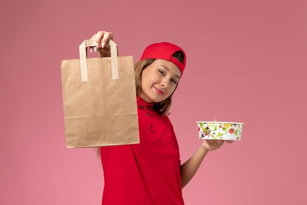 Weiblicher kurier der vorderansicht in der roten uniform und im umhang, die lieferung-nahrungsmittelpaket und schüssel auf der rosa wand halten, uniform-zustellungsjob-servicearbeiter