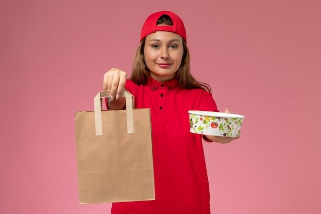 Weiblicher kurier der vorderansicht in der roten uniform und im umhang, die lieferung nahrungsmittelpaket und schüssel auf hellrosa wand halten, einheitlicher zustellungsjobdienst