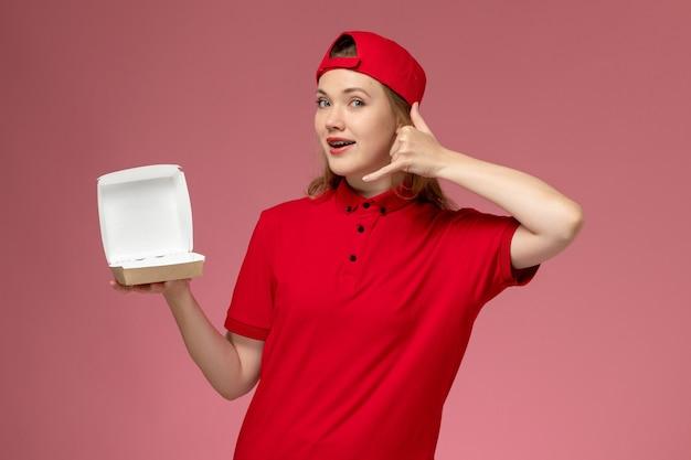 Weiblicher kurier der vorderansicht in der roten uniform und im umhang, die wenig leeres liefernahrungsmittelpaket auf uniformjob des rosa schreibtischlieferdienstes halten