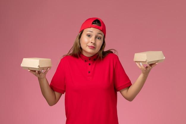 Weiblicher kurier der vorderansicht in der roten uniform und im umhang, die zustellungsnahrungsmittelpakete auf hellrosa wand halten, einheitliche zustelldienstfirma arbeiten