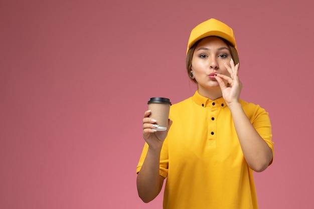 Weiblicher kurier der vorderansicht in gelbem uniformgelbumhang, der braune plastikkaffeetasse hält, die leckeres zeichen auf der weiblichen farbe der rosa schreibtischuniformlieferung zeigt