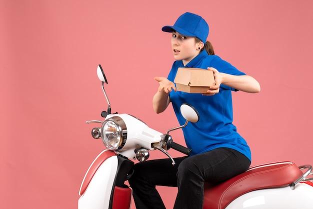 Weiblicher kurier der vorderansicht mit kleinem nahrungsmittelpaket auf rosa einheitlichem arbeiterlebensmittel-lieferfahrrad