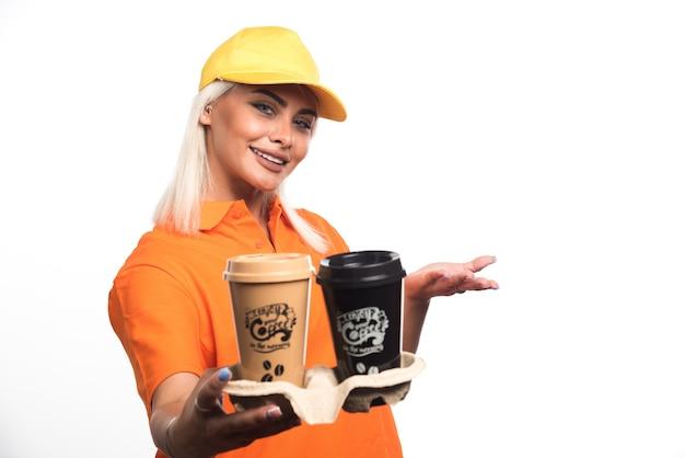 Weiblicher kurier, der zwei tassen kaffee auf weißem hintergrund beim lächeln hält. hochwertiges foto
