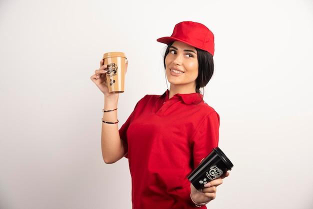 Weiblicher kurier, der zwei tassen kaffee auf weißem hintergrund hält. hochwertiges foto