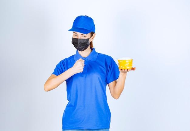 Weiblicher kurier des restaurants in blauer uniform und gesichtsmaske, der ein essen zum mitnehmen liefert und den guten geschmack garantiert.