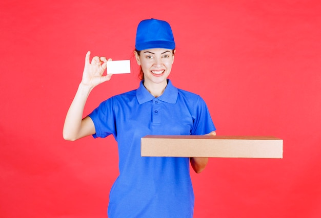 Weiblicher kurier in blauer uniform, der einen karton hält und ihre visitenkarte vorlegt.
