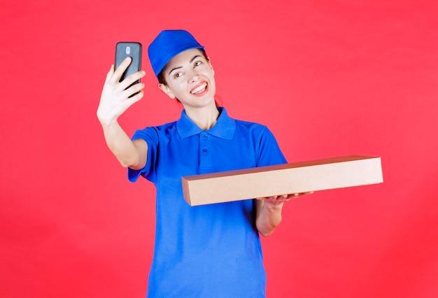 Weiblicher kurier in blauer uniform, der einen pizzakarton zum mitnehmen aus pappe hält und ihr selfie macht.