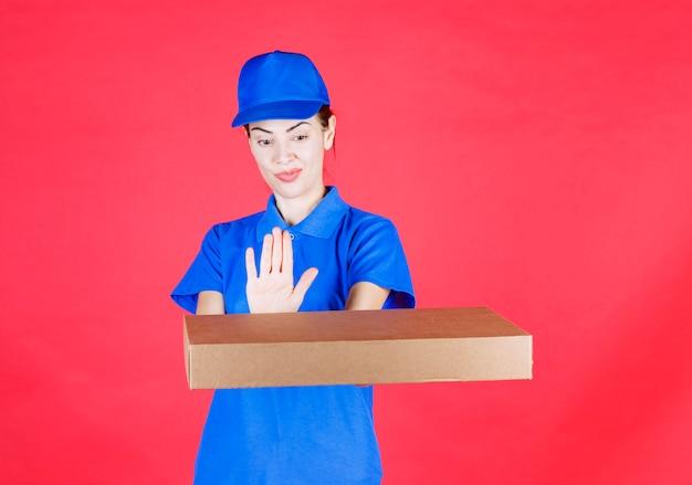 Weiblicher kurier in blauer uniform, der einen pizzakarton zum mitnehmen aus pappe hält und sich weigert, ihn zu nehmen.