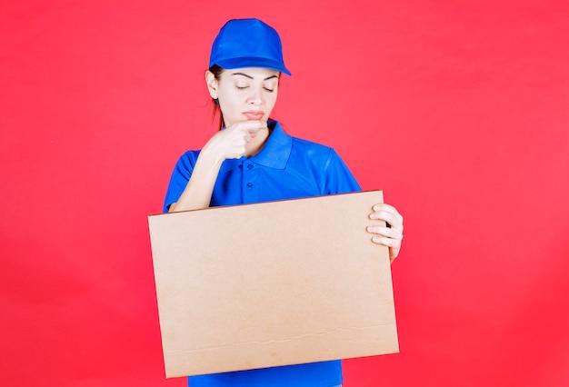 Weiblicher kurier in blauer uniform, der einen pizzakarton zum mitnehmen aus pappe hält und verwirrt denkt oder schaut.