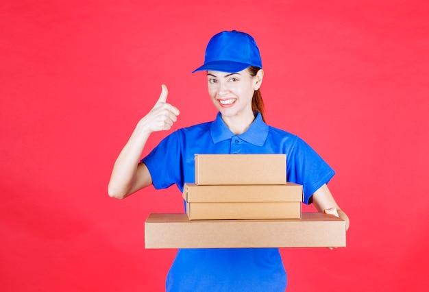 Weiblicher kurier in blauer uniform, der einen vorrat an kartons hält und ein genusszeichen zeigt.