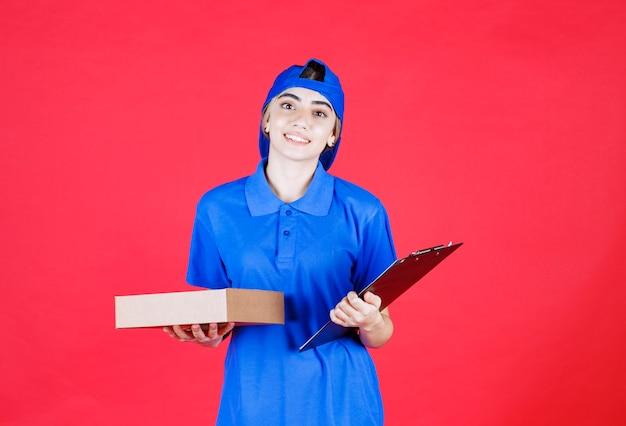 Weiblicher kurier in blauer uniform, die eine checkliste und eine imbissbox hält.