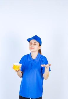 Weiblicher kurier in blauer uniform, die eine nudelbecher zum mitnehmen hält und das essen riecht.