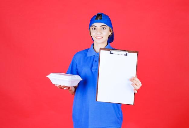 Weiblicher kurier in blauer uniform, die eine weiße imbissbox hält und die checkliste zur unterschrift vorlegt