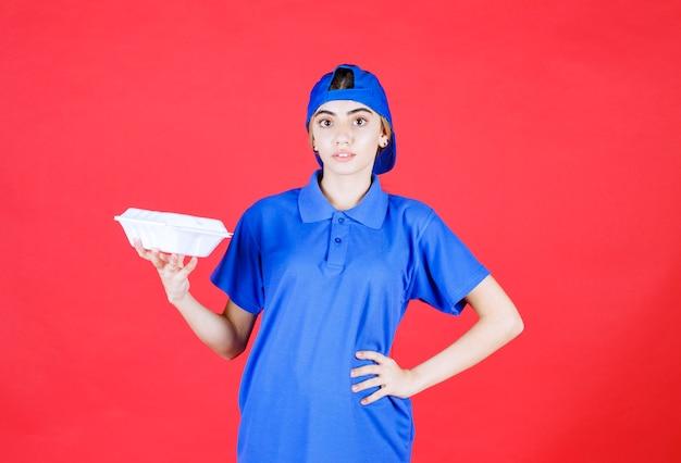 Weiblicher kurier in blauer uniform, die eine weiße imbissbox hält.
