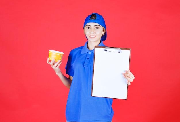 Weiblicher kurier in blauer uniform, die einen gelben nudelbecher hält und die taskliste zur unterschrift präsentiert.