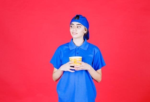 Weiblicher kurier in blauer uniform, die einen gelben nudelbecher hält.