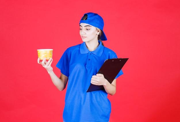 Weiblicher kurier in blauer uniform, die einen gelben nudelbecher und einen schwarzen ordner hält.