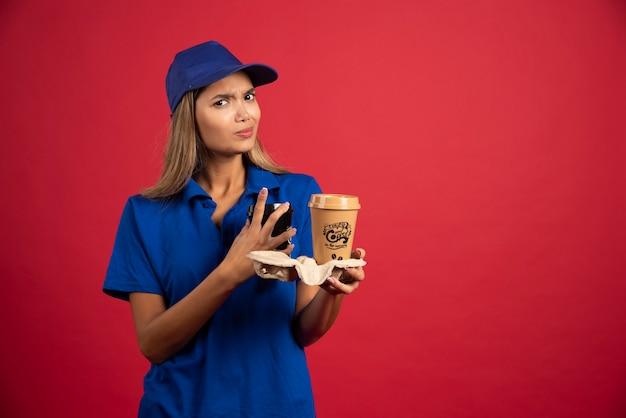 Weiblicher kurier in blauer uniform, die einen karton von zwei tassen hält.