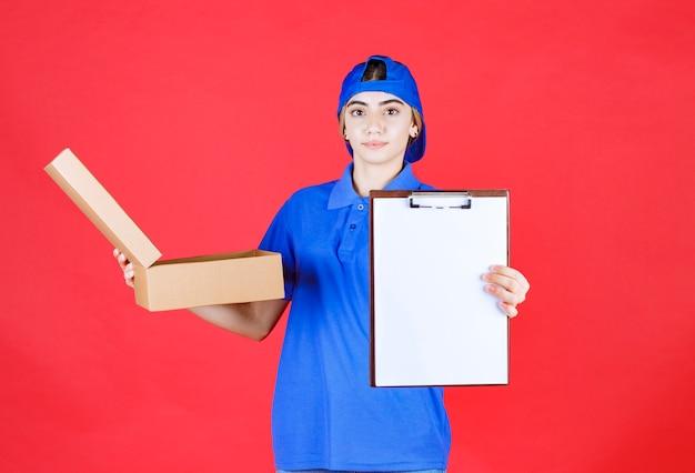 Weiblicher kurier in blauer uniform, die einen offenen pappkarton zum mitnehmen hält und die taskliste zur unterschrift vorlegt.