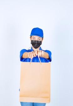 Weiblicher kurier in blauer uniform und gesichtsmaske, der dem kunden eine einkaufstüte aus karton liefert.