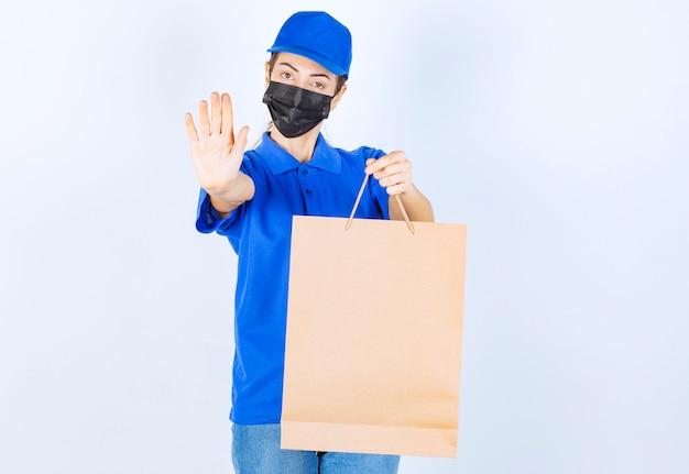 Weiblicher kurier in blauer uniform und gesichtsmaske, der eine einkaufstüte aus pappe hält und sich weigert, etwas anderes zu nehmen.