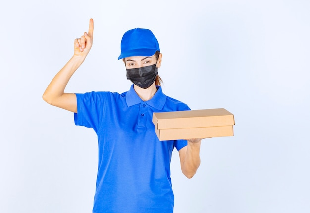 Weiblicher kurier in blauer uniform und gesichtsmaske, der einen karton hält und auf irgendwo zeigt.